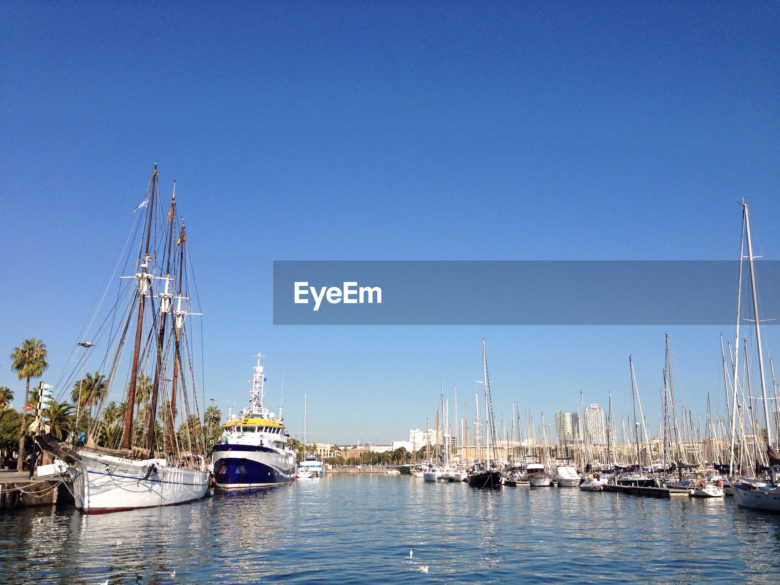 Sailboats moored in lake against clear blue sky