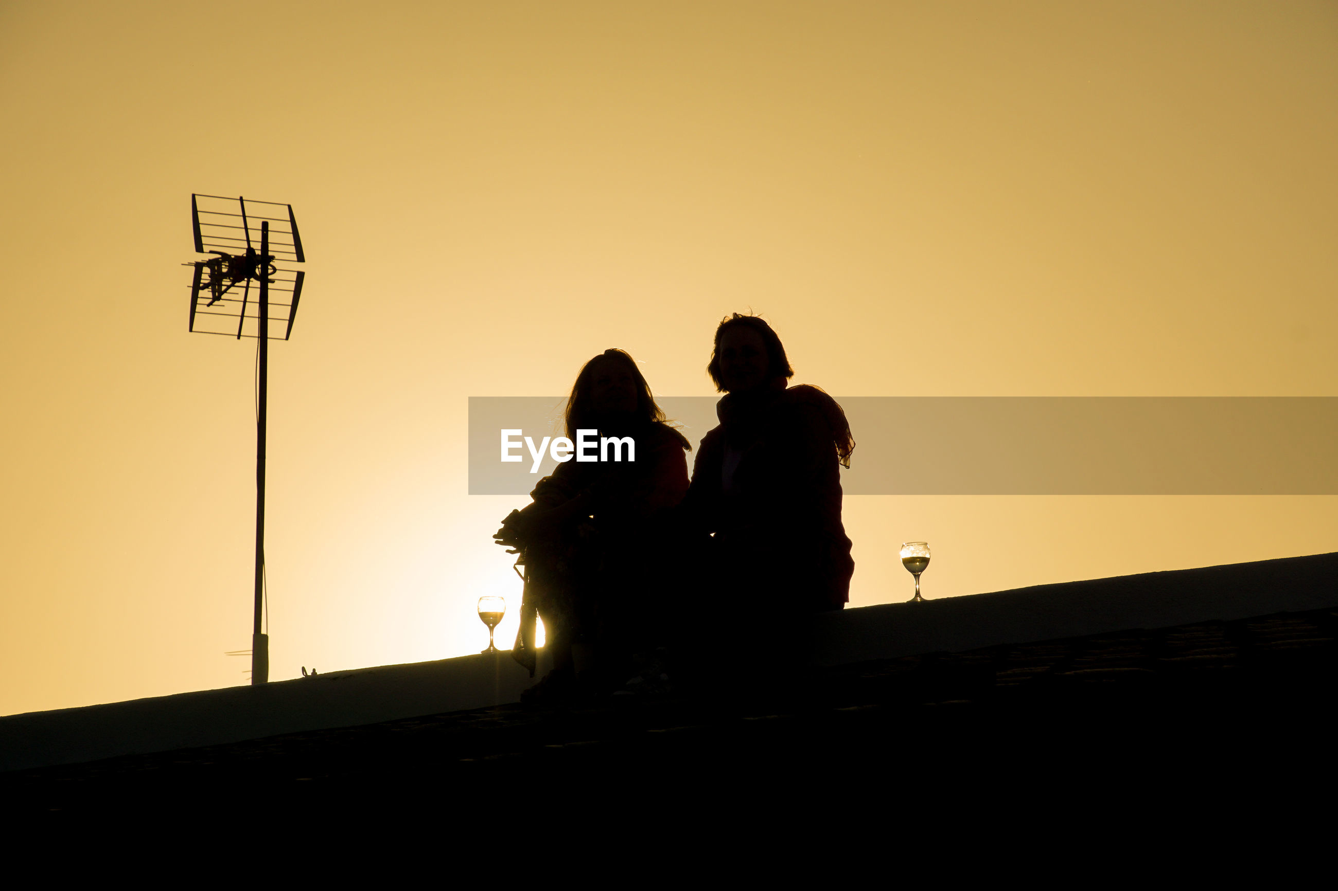 Low angle view of silhouette of people on roof against sky