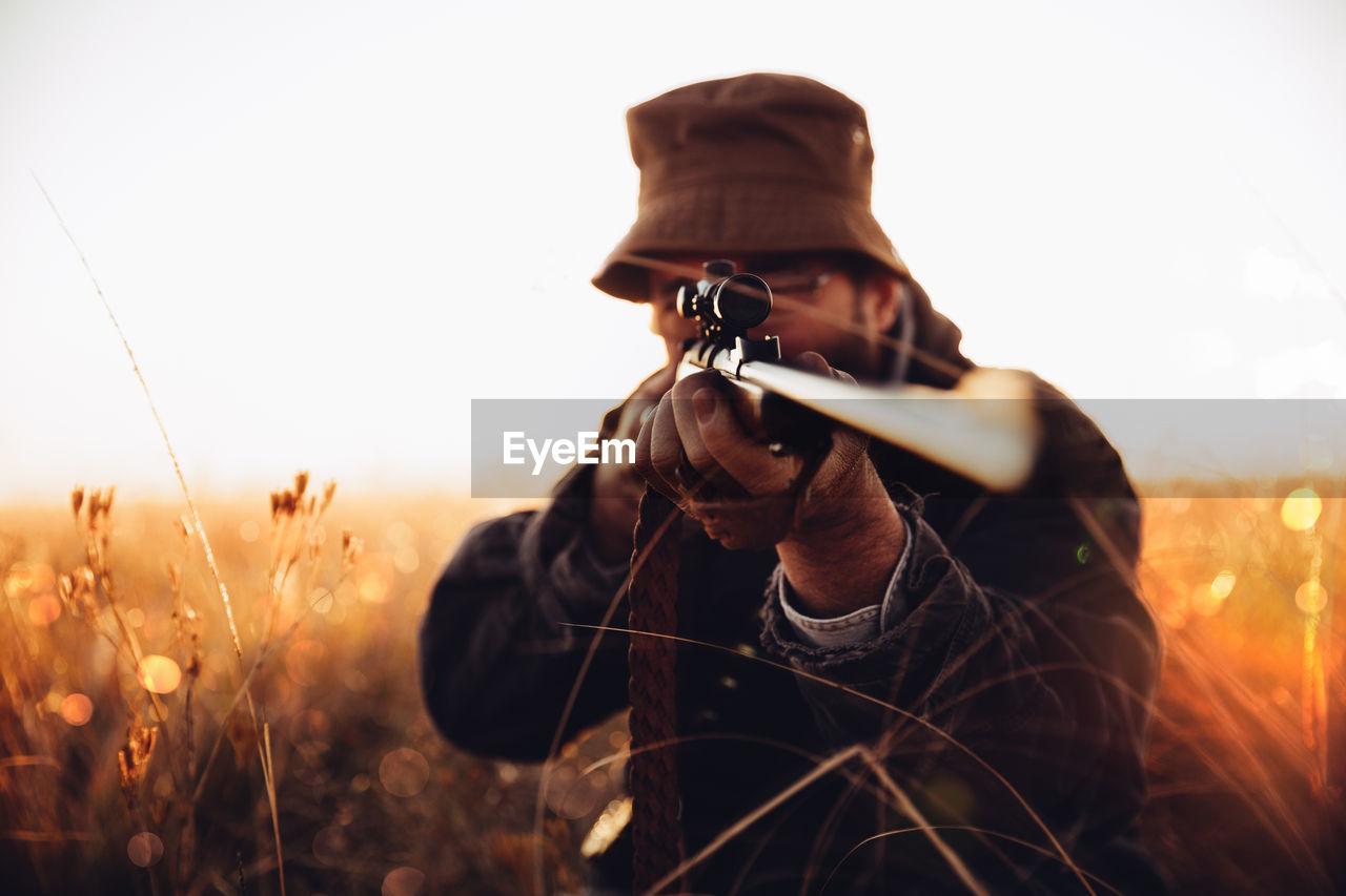 Man Aiming Rifle On Field Against Sky