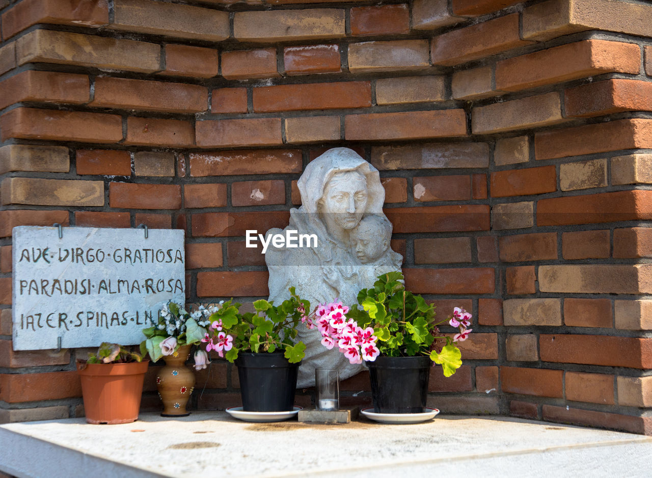 flower, brick wall, statue, sculpture, outdoors, day, no people