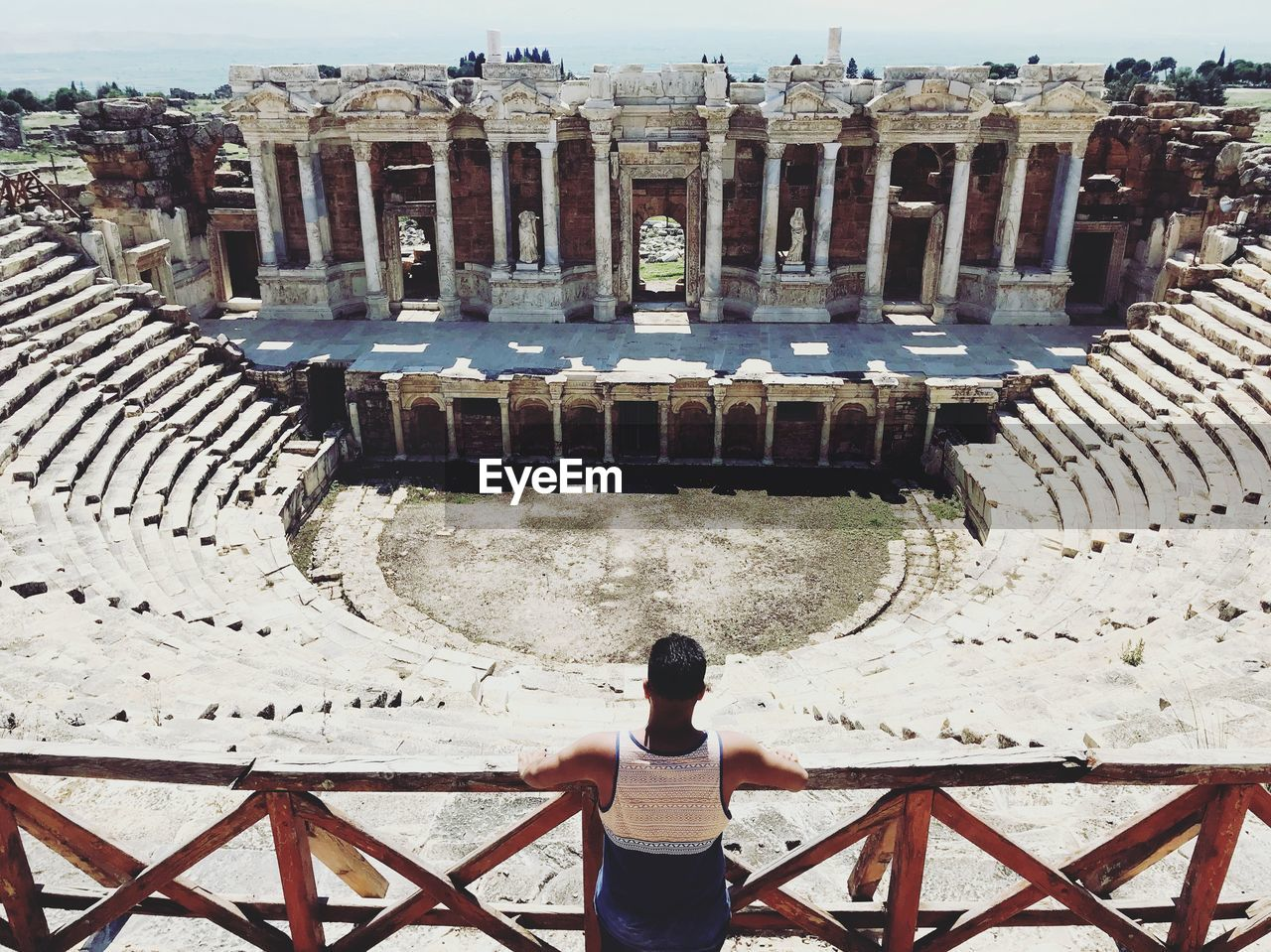architecture, rear view, tourism, ancient, real people, lifestyles, built structure, history, travel destinations, leisure activity, the past, day, amphitheater, arts culture and entertainment, high angle view, travel, old ruin, one person, women, outdoors, ancient civilization, archaeology, architectural column, ruined