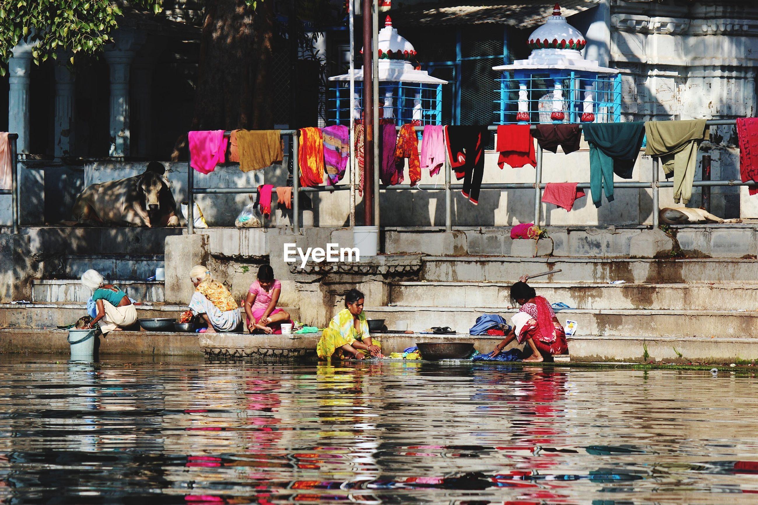 Women doing laundry near lake against temples