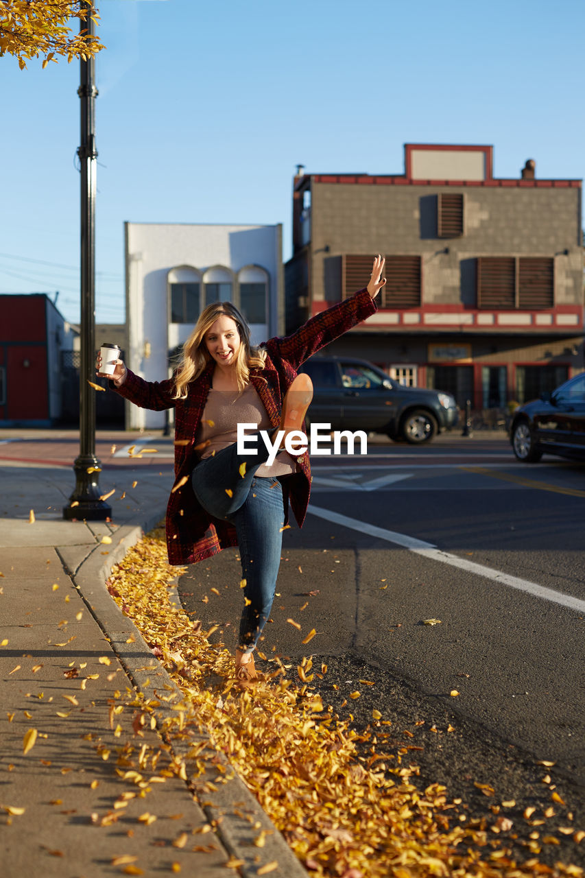 Young Woman Playing With Autumn Leaves On Road In City