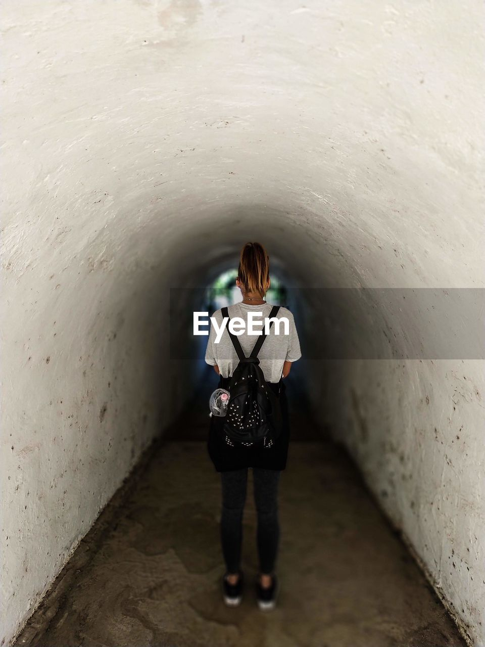 full length, one person, real people, rear view, lifestyles, architecture, wall - building feature, standing, casual clothing, leisure activity, women, indoors, built structure, adult, tunnel, day, the way forward, young adult, direction, hairstyle