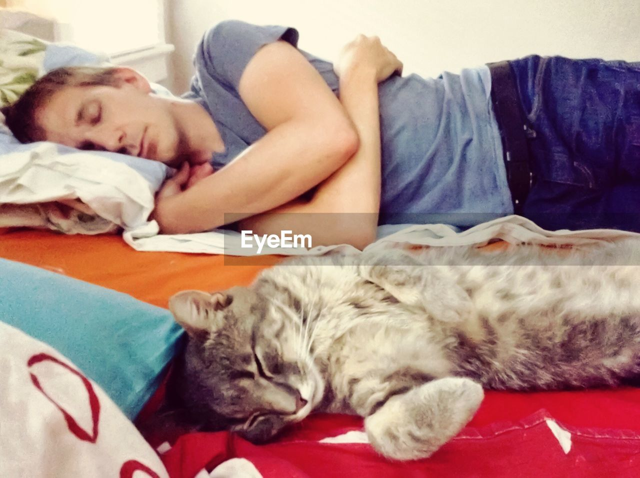 Man and cat sleeping on bed