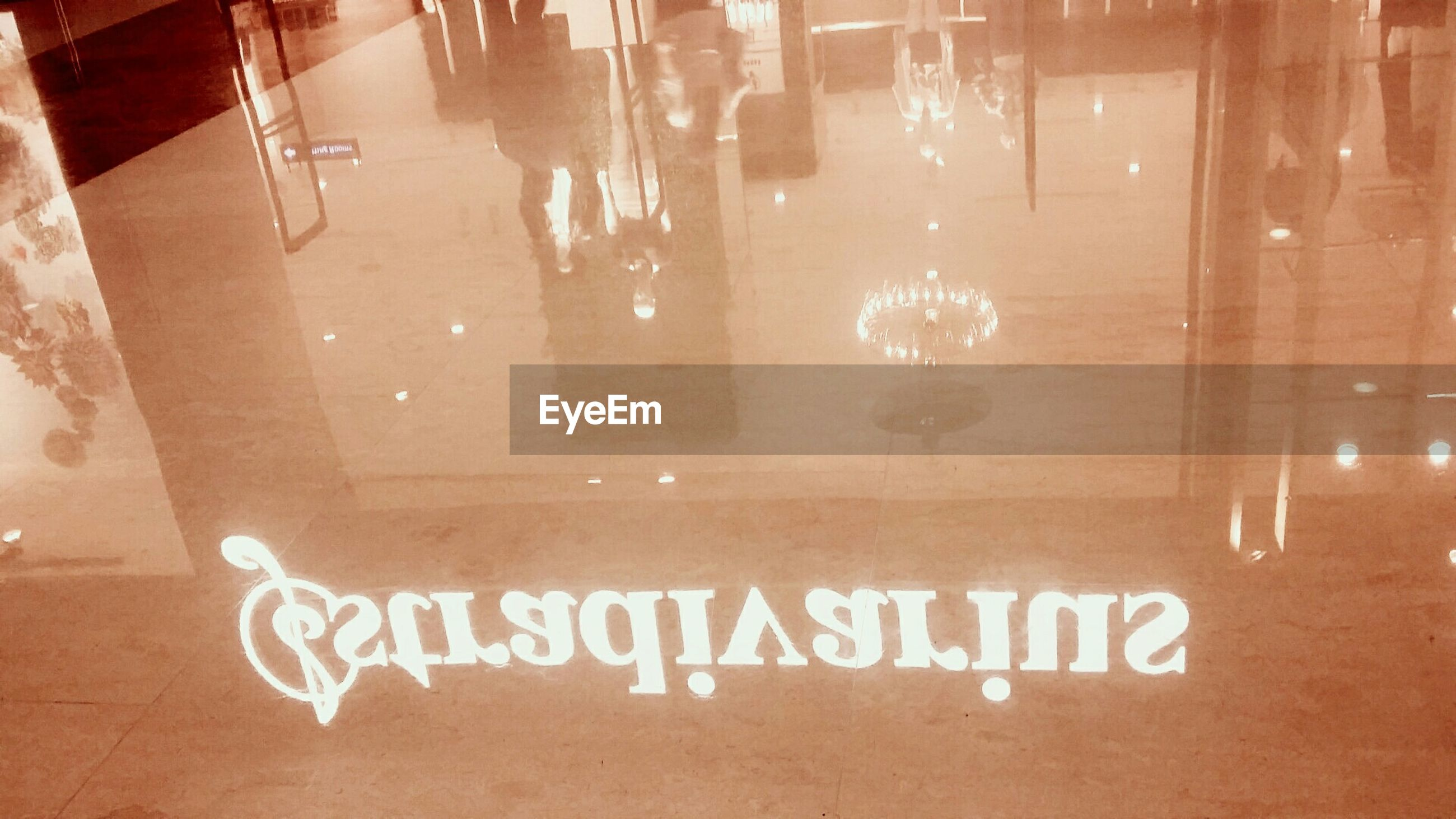 indoors, glass - material, reflection, transparent, flooring, window, water, tiled floor, text, built structure, wet, wall - building feature, communication, architecture, western script, tile, empty, illuminated, high angle view, no people