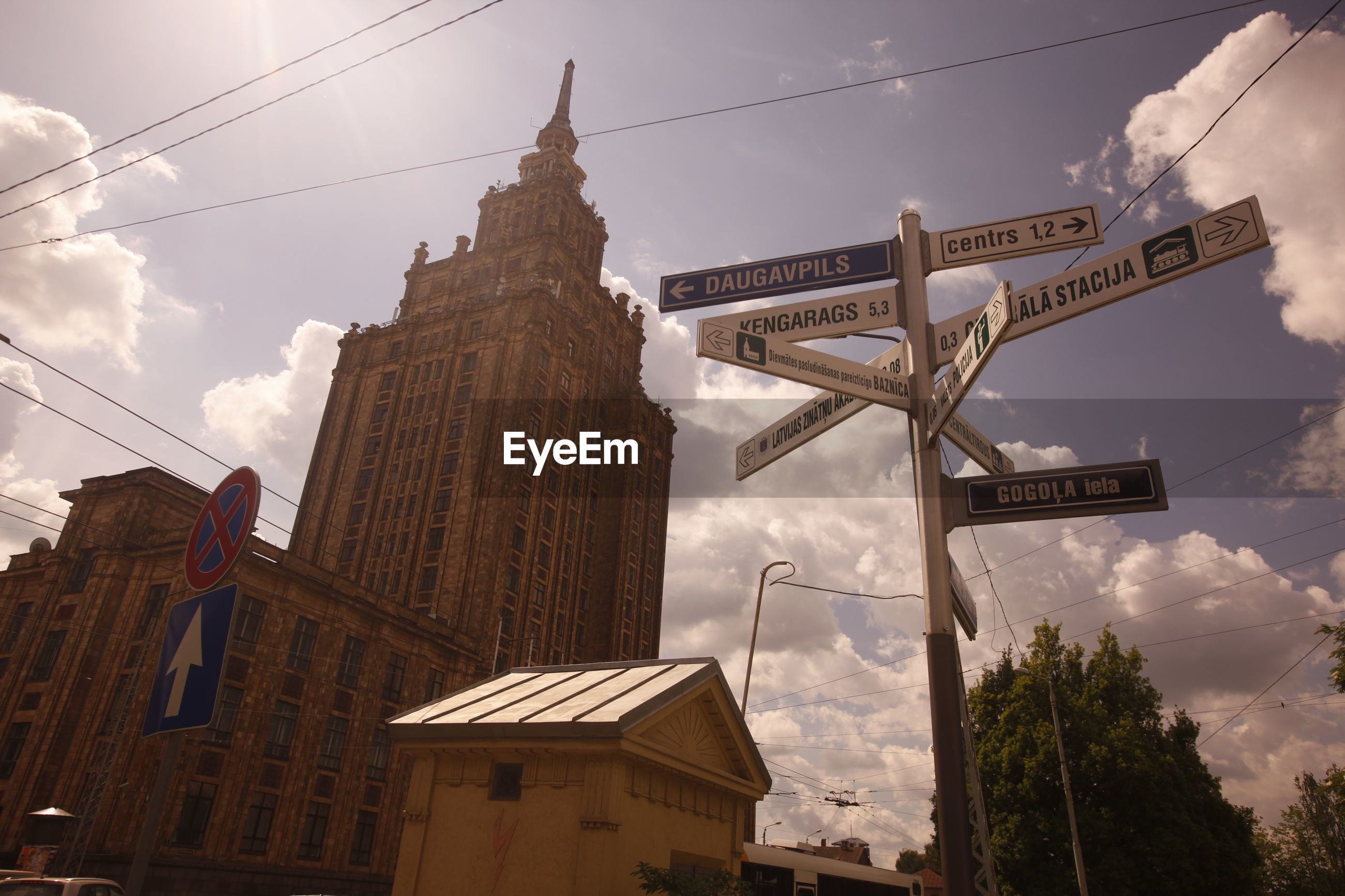 Low angle view of road sign boards and latvian academy of sciences against sky