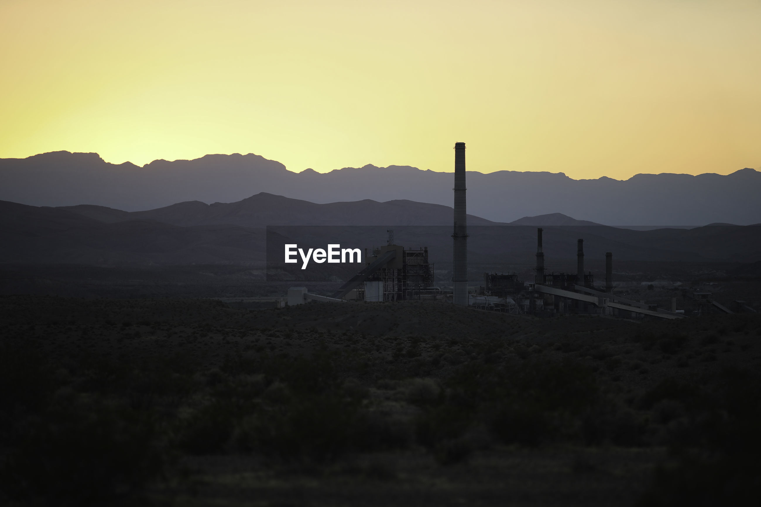 Sunset over a mountain and factory near the border of arizona.