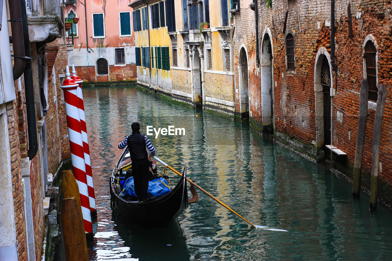 Rear View Of Man On Gondola In Canal