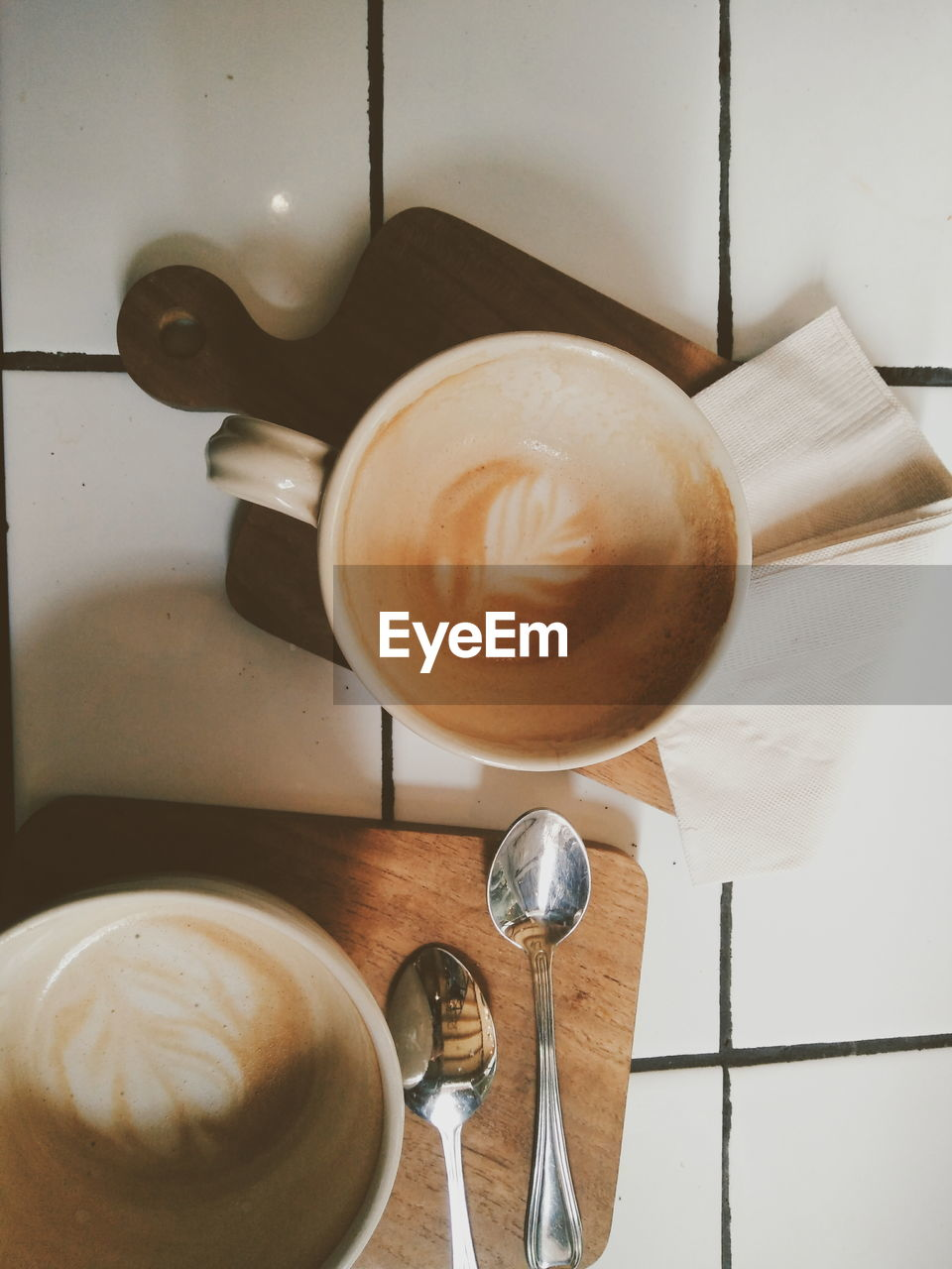 Directly Above Shot Of Coffee Cup On Cutting Board Over Floor