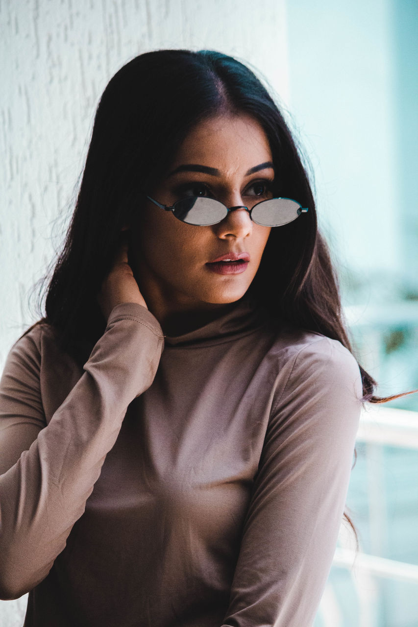 Fashionable young woman wearing sunglasses while looking away against wall