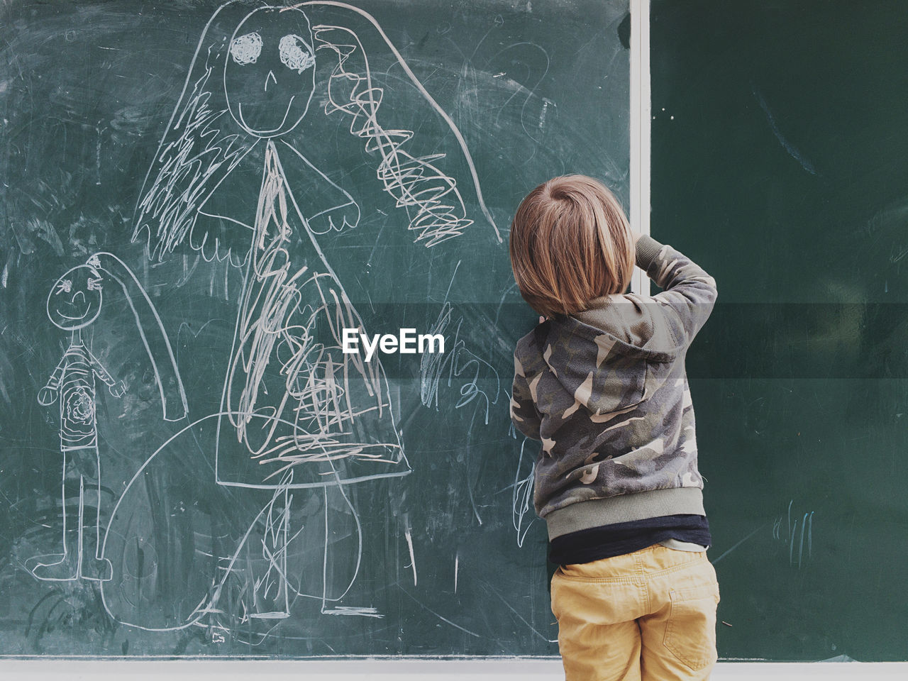 Rear view of boy drawing on blackboard at classroom