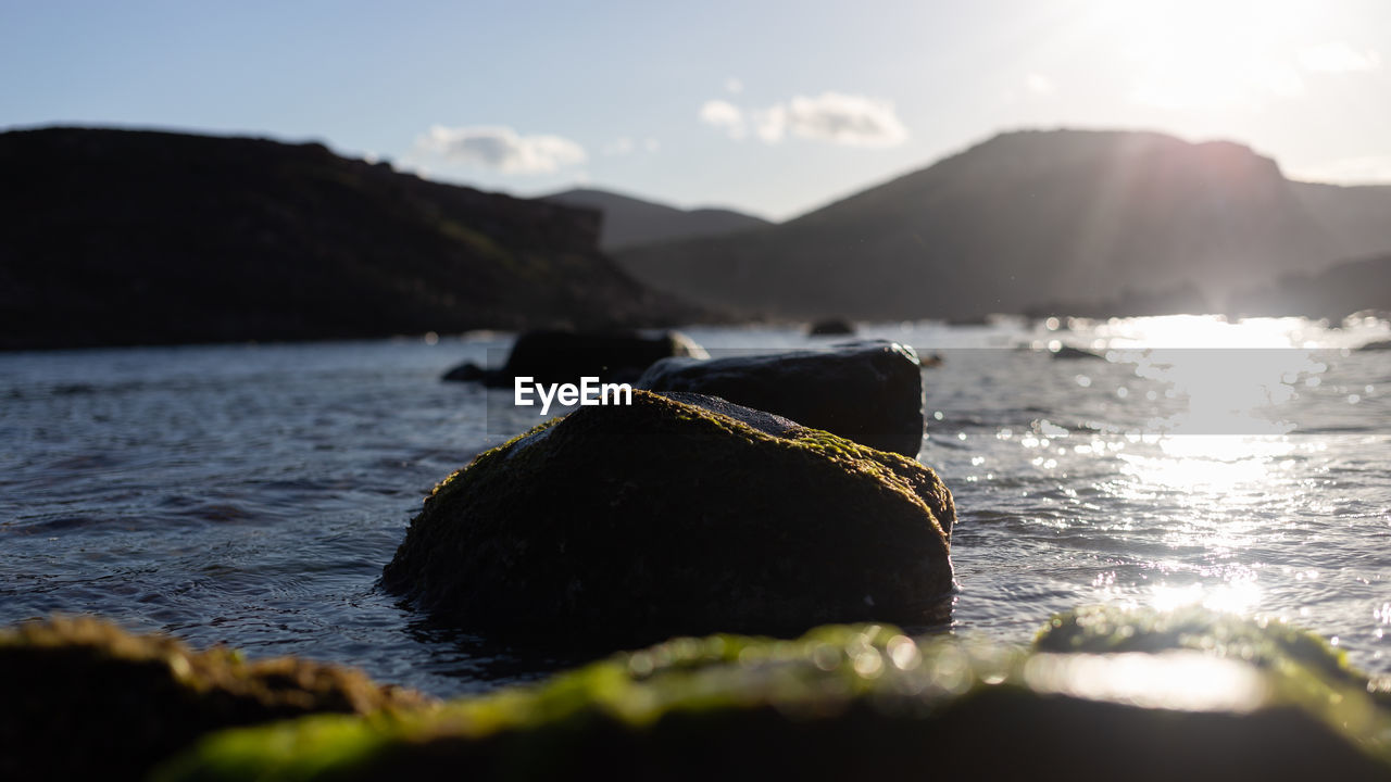 water, mountain, sky, selective focus, rock, nature, sea, beauty in nature, tranquility, scenics - nature, solid, rock - object, sunlight, no people, day, beach, tranquil scene, outdoors, land, surface level, lens flare