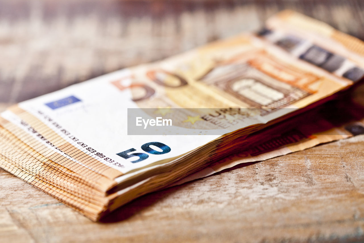 still life, close-up, table, selective focus, no people, wood - material, wealth, indoors, paper currency, finance, currency, focus on foreground, business, high angle view, number, communication, text, day, education, savings, economy