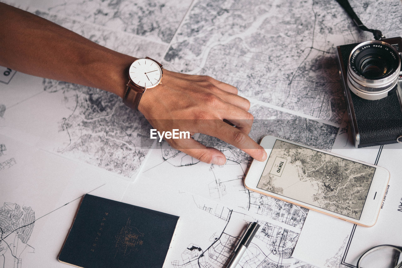 Cropped Image Of Hand Using Phone Over World Map By Camera