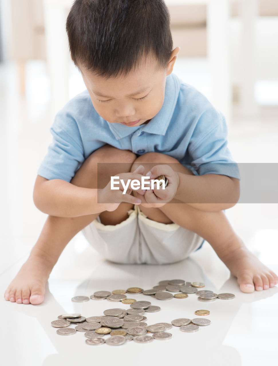 Full Length Of Boy Counting Coins While Sitting On Tiled Floor At Home