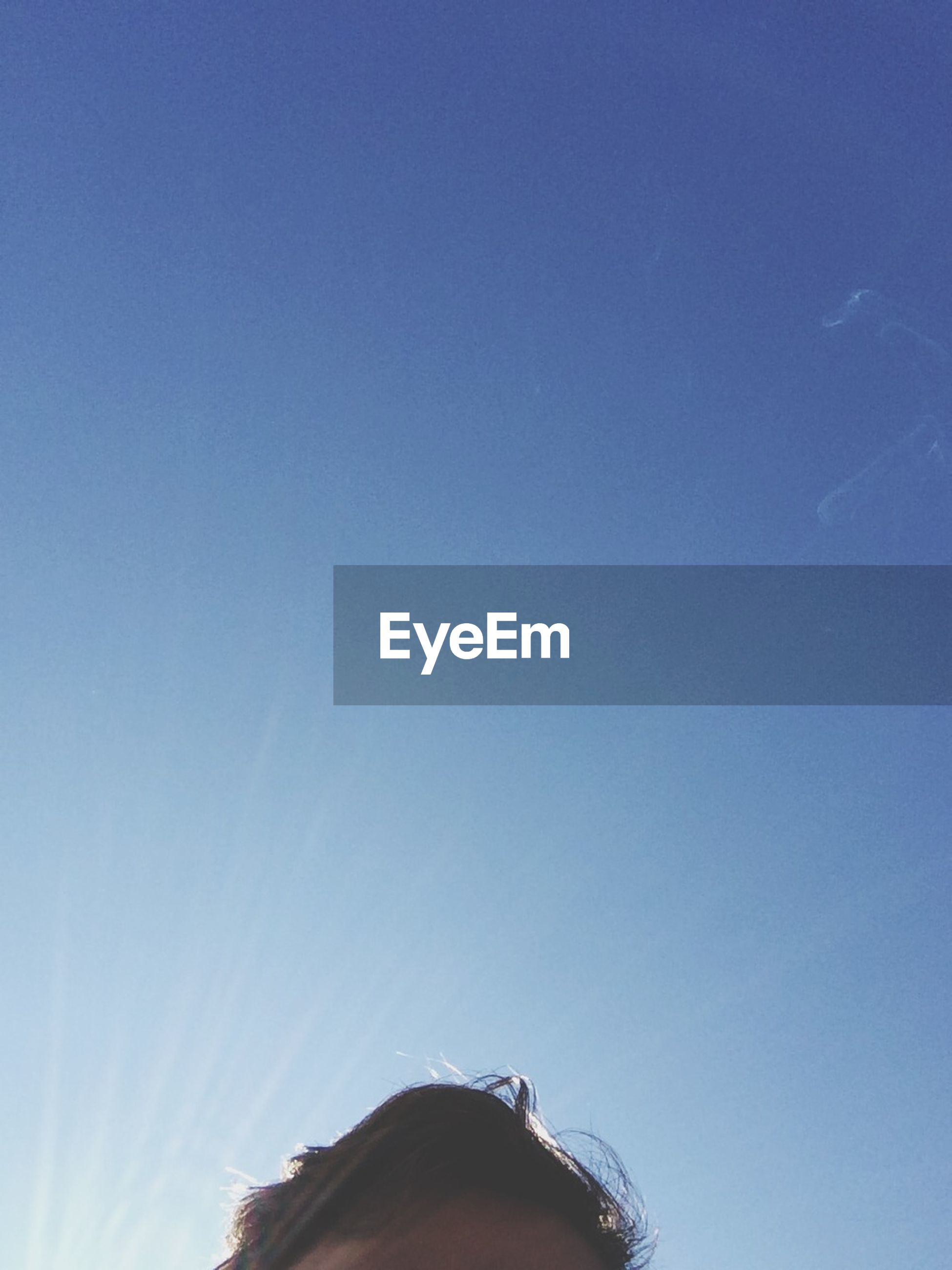 Man's head against blue sky