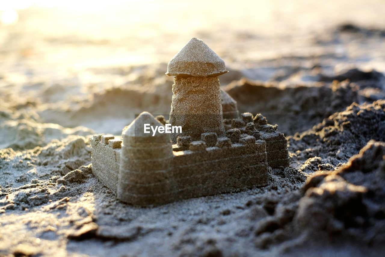 selective focus, beach, land, nature, sand, day, no people, close-up, sea, sunlight, focus on foreground, outdoors, water, creativity, sandcastle, solid, winter, abandoned, beauty in nature, art and craft