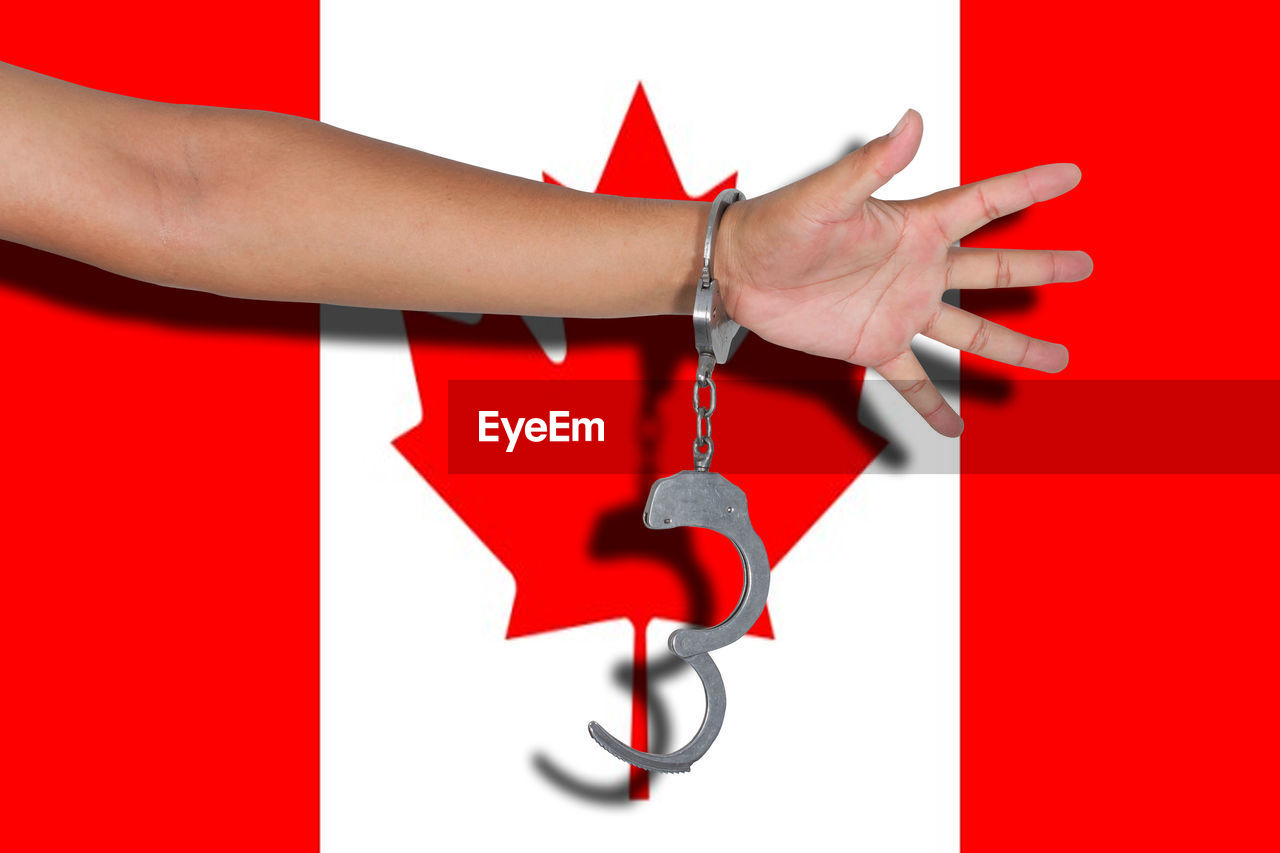 Cropped hand of person wearing handcuffs against flag
