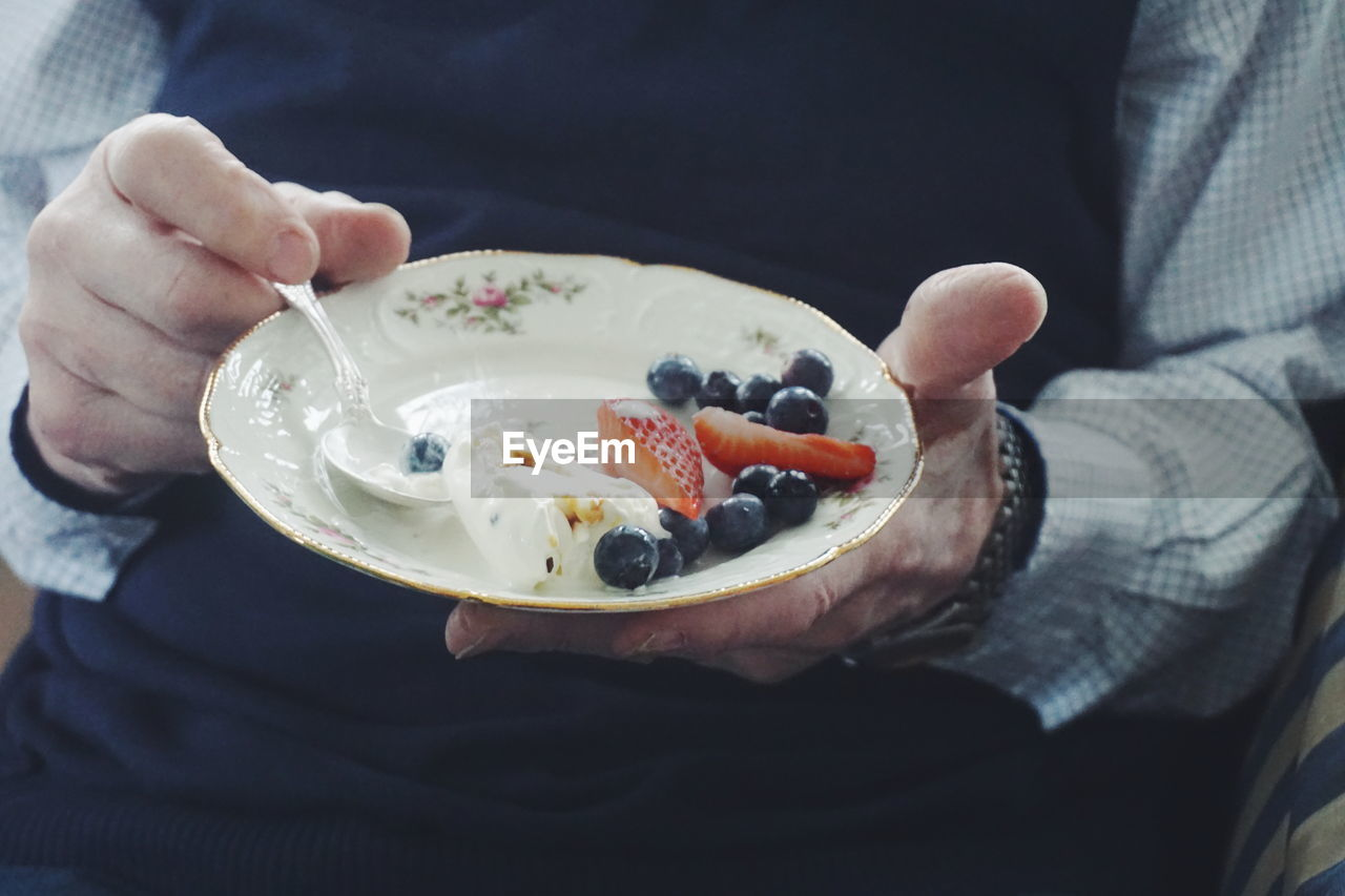 Midsection of man eating fresh fruits in plate