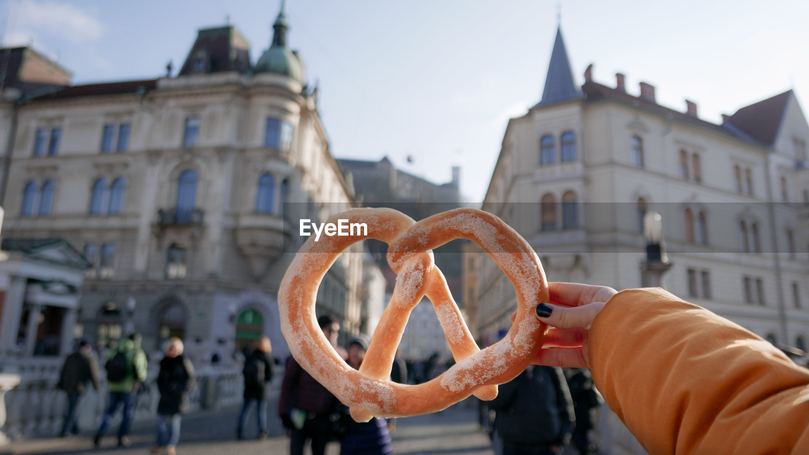 Hand holding pretzel against building in city.