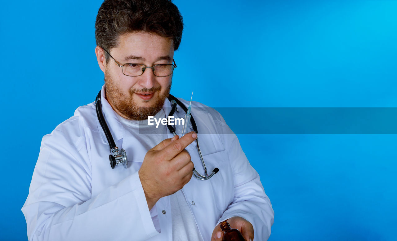 doctor, occupation, stethoscope, medical supplies, one person, healthcare and medicine, medical instrument, front view, blue, medical equipment, lab coat, eyeglasses, glasses, holding, clothing, men, real people, young adult, adult, blue background