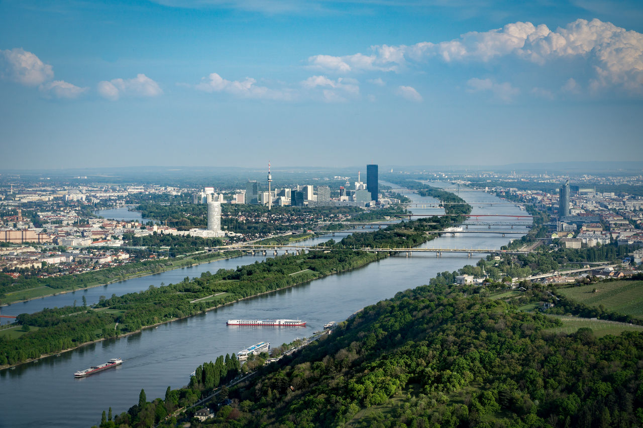 High angle view of river by cityscape against sky