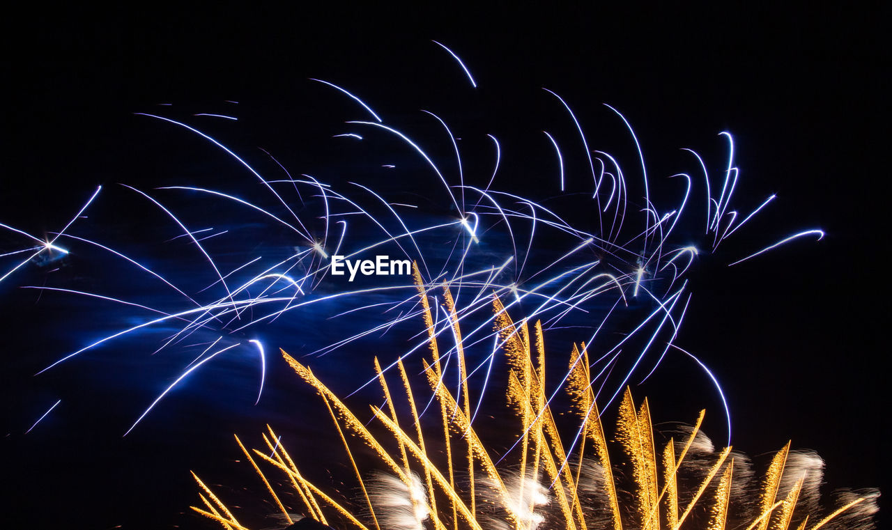 night, illuminated, long exposure, motion, blurred motion, glowing, celebration, arts culture and entertainment, low angle view, no people, firework, sky, light, event, nature, light trail, sparks, light - natural phenomenon, firework display, pattern, firework - man made object, black background