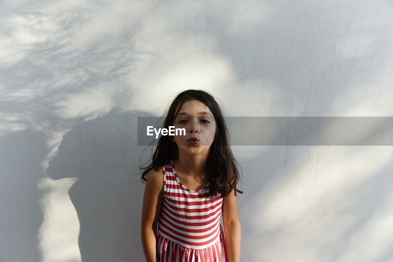 Portrait Of Girl Puckering Lips While Standing Against White Wall