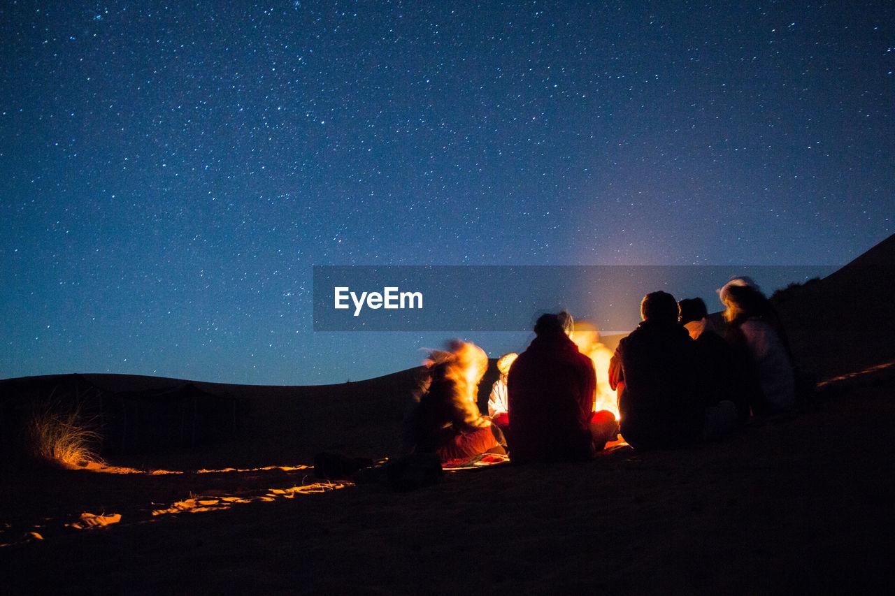 People Enjoying Campfire In Desert At Night