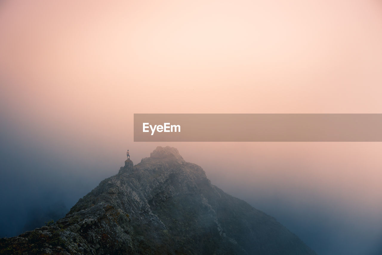 ROCK FORMATIONS ON MOUNTAIN AGAINST SKY DURING SUNSET
