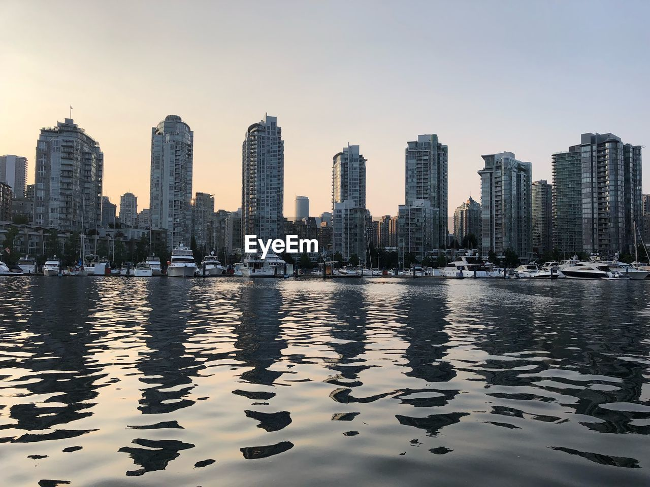 Scenic View Of River And Buildings Against Sky In City