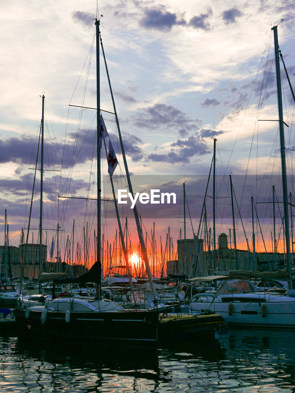 Sailboats moored in harbor against sky during sunset