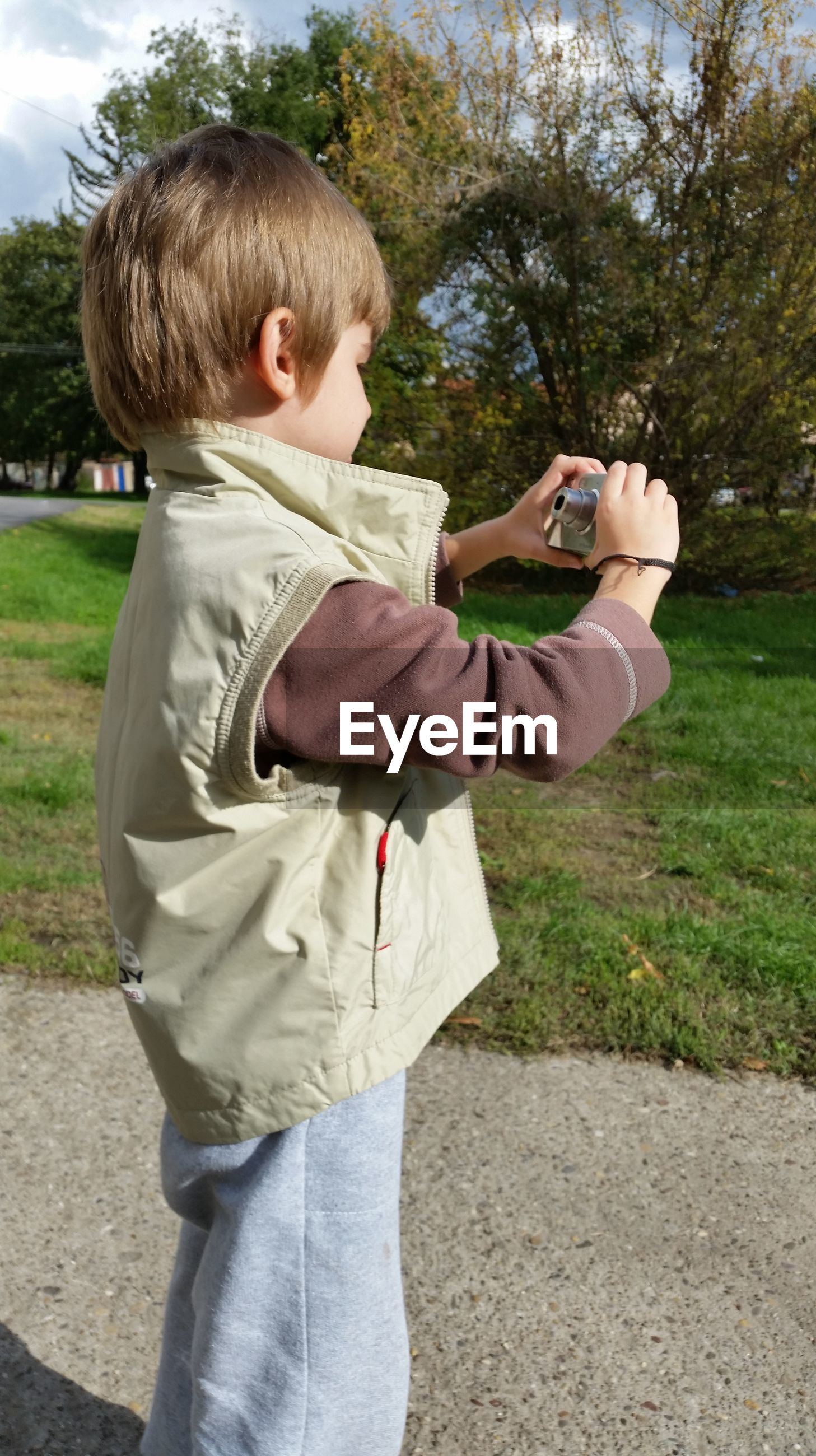 Side view of boy photographing with camera on footpath
