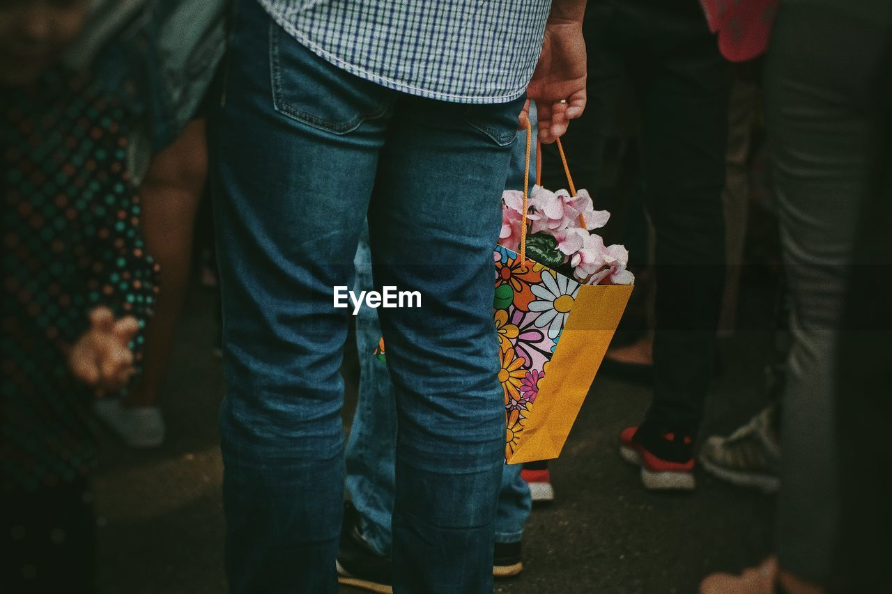 Midsection of man holding bag with flowers