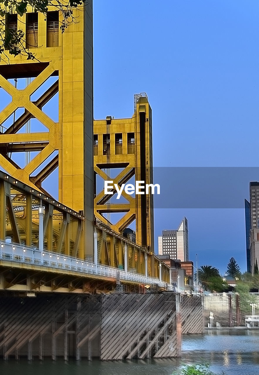 architecture, built structure, building exterior, clear sky, blue, water, no people, outdoors, bridge - man made structure, day, river, low angle view, sky, city
