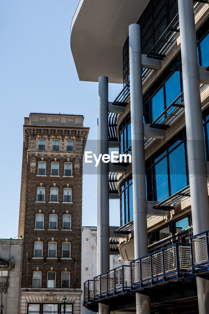 architecture, built structure, building exterior, window, building, sky, low angle view, no people, clear sky, day, residential district, nature, city, outdoors, glass - material, sunlight, blue, fire escape, modern, balcony, apartment