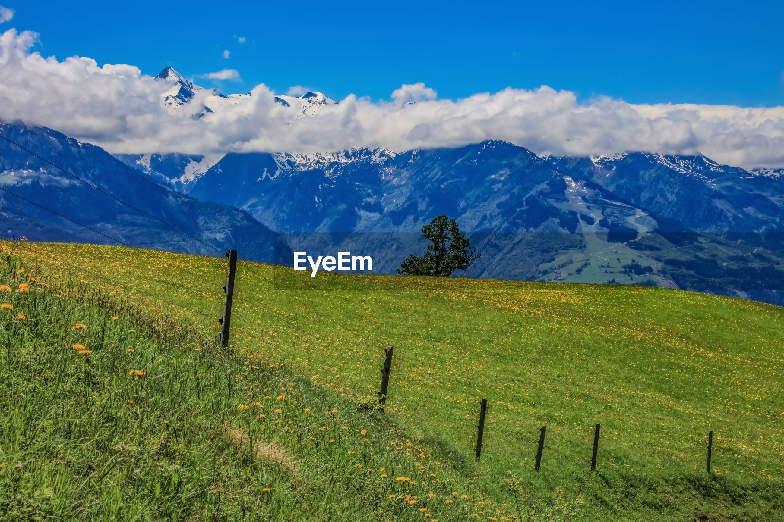 SCENIC VIEW OF FIELD SEEN THROUGH MOUNTAINS