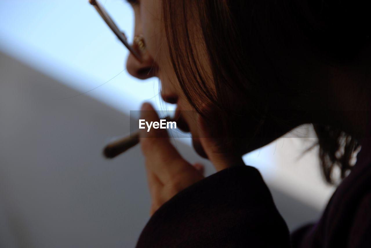 Close-Up Of Woman Smoking Marijuana Joint
