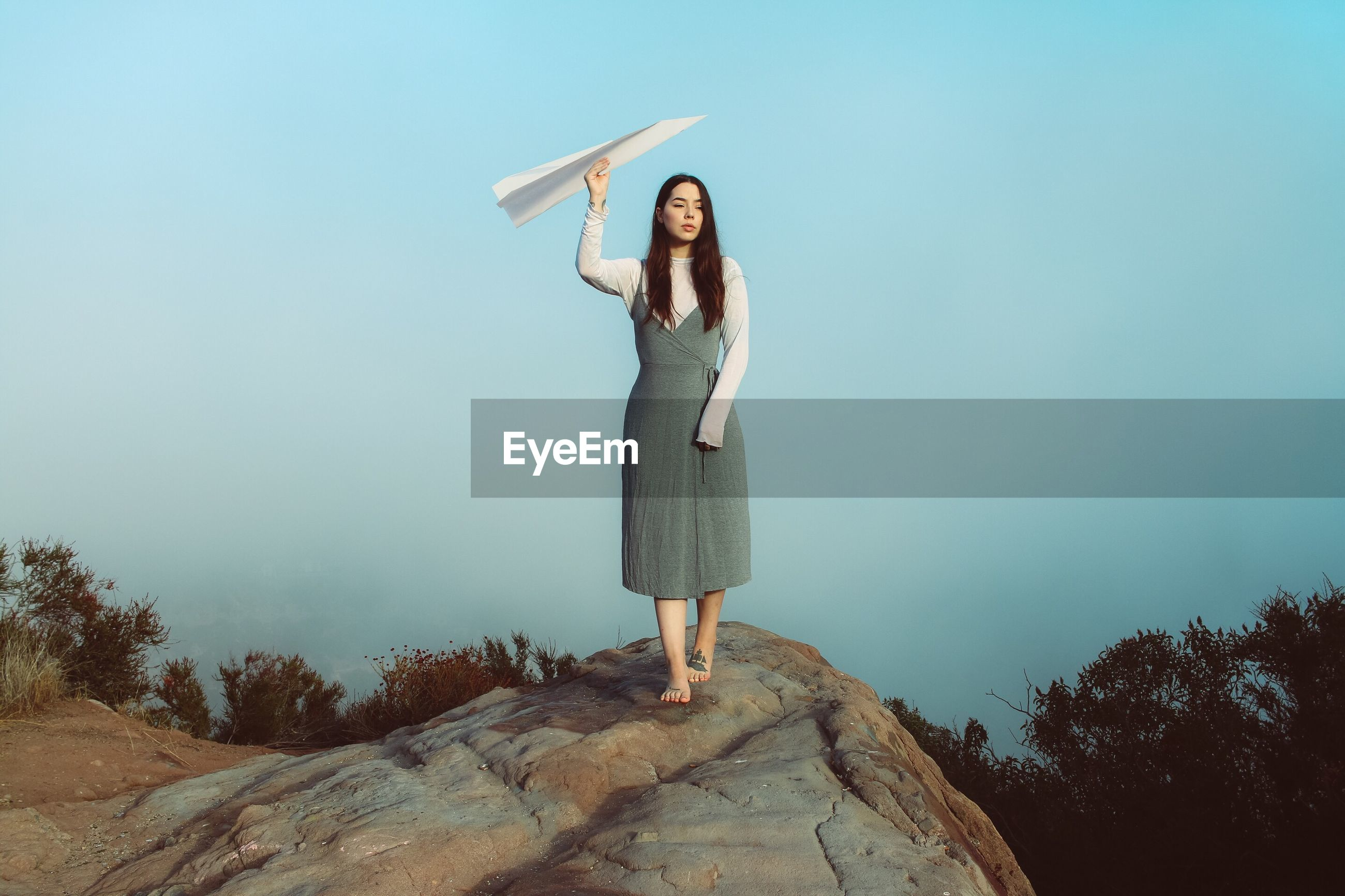 Woman holding paper airplane while walking on rock against sky during sunset