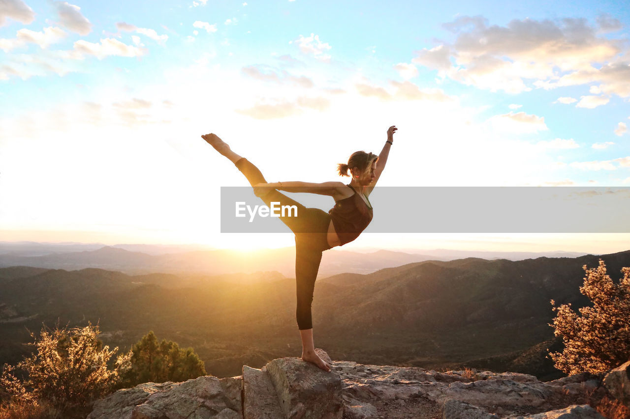Woman balancing on rock at mountain against sky during sunset