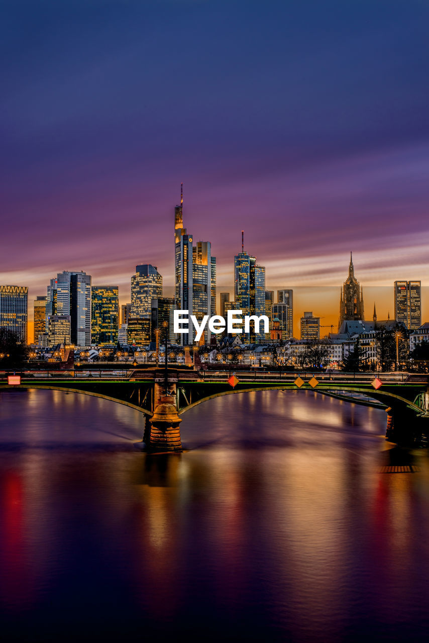 Illuminated bridge over river by buildings against sky at sunset in frankfurt, germany.