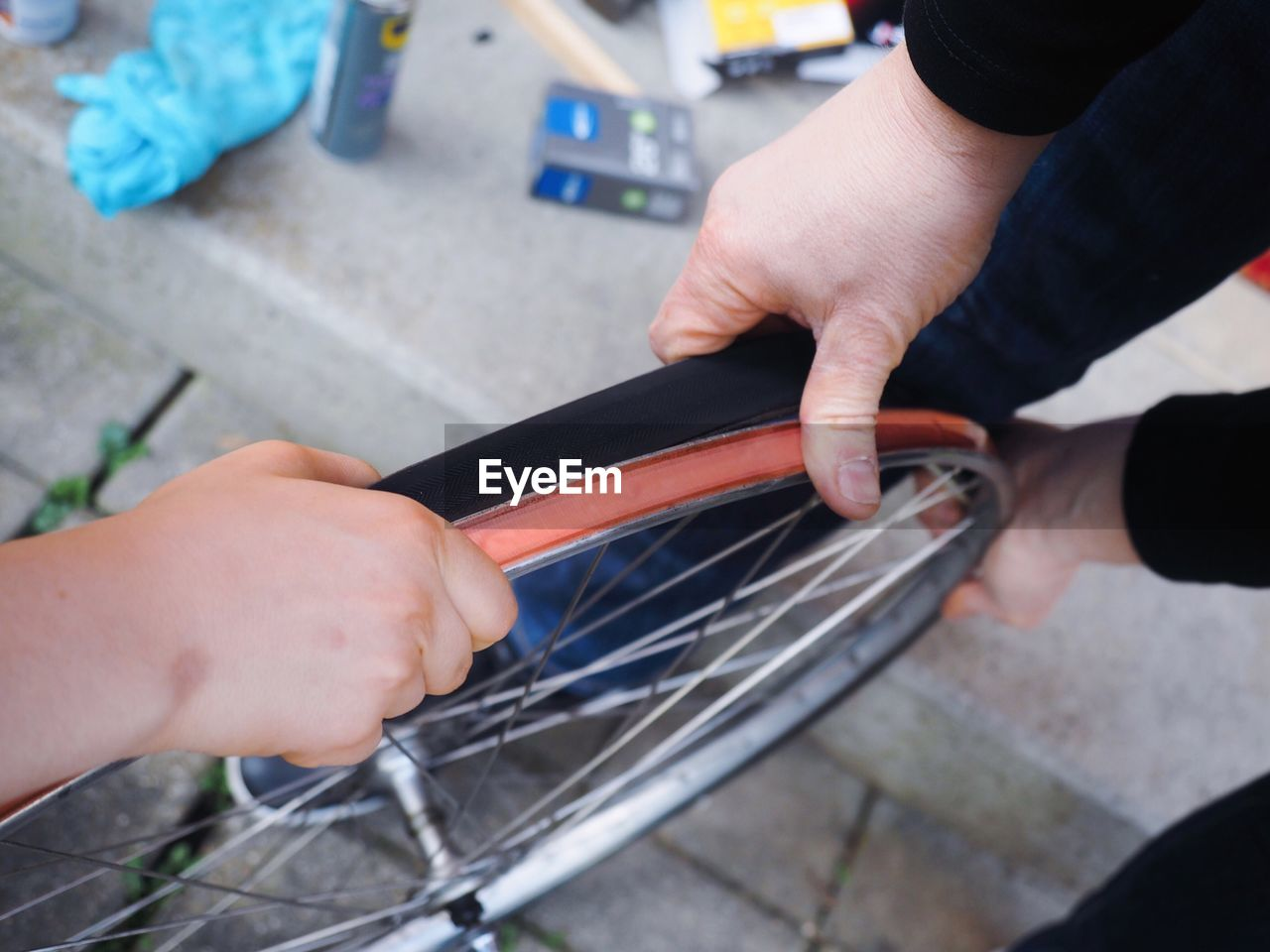 High Angle View Of Hands Repairing Bicycle Wheel