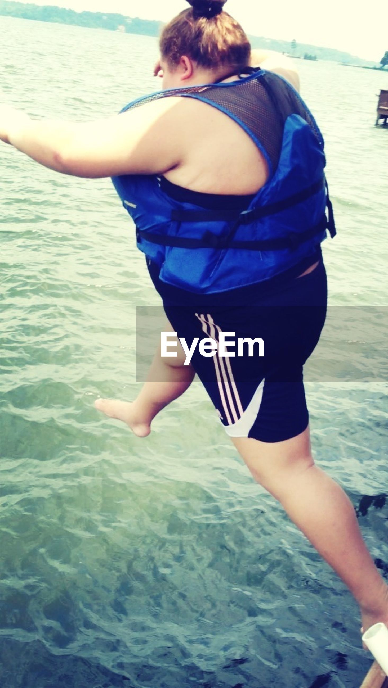 water, sea, lifestyles, leisure activity, person, casual clothing, waterfront, standing, day, beach, three quarter length, vacations, young adult, rippled, outdoors, side view, lake, holding