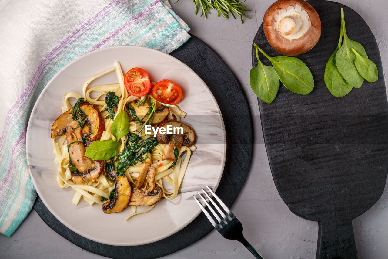 Udon with mushrooms and spinach in a plate on a napkin on a concrete background near