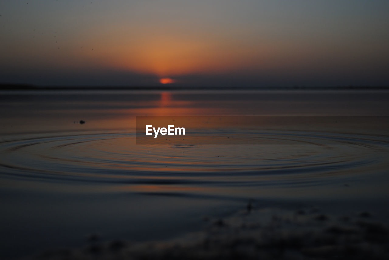 sunset, sky, water, tranquil scene, tranquility, beauty in nature, scenics - nature, orange color, nature, no people, reflection, sea, outdoors, idyllic, waterfront, focus on foreground, silhouette, circle, selective focus, purity