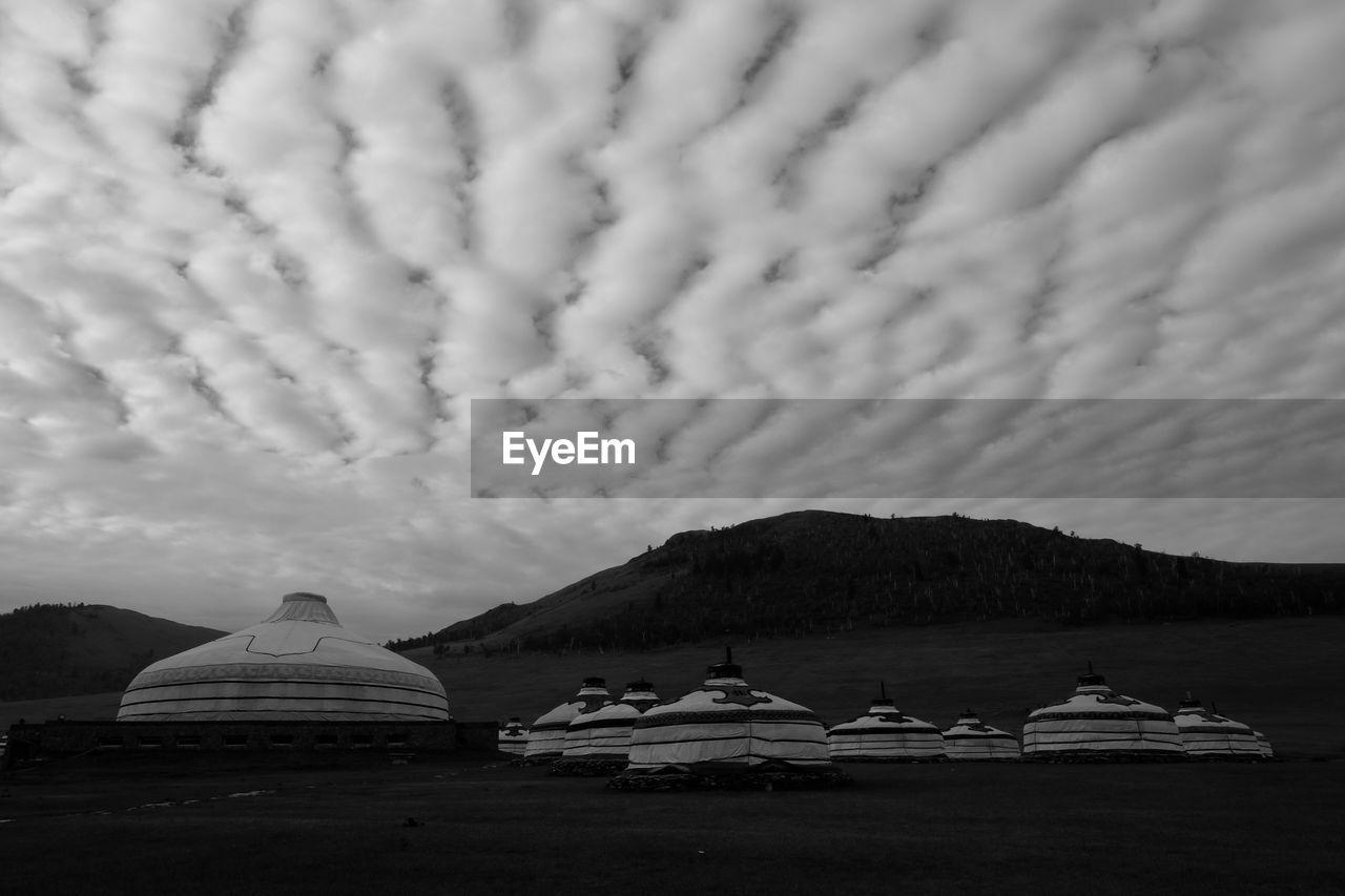 Built Structures On Landscape Against Cloudy Sky