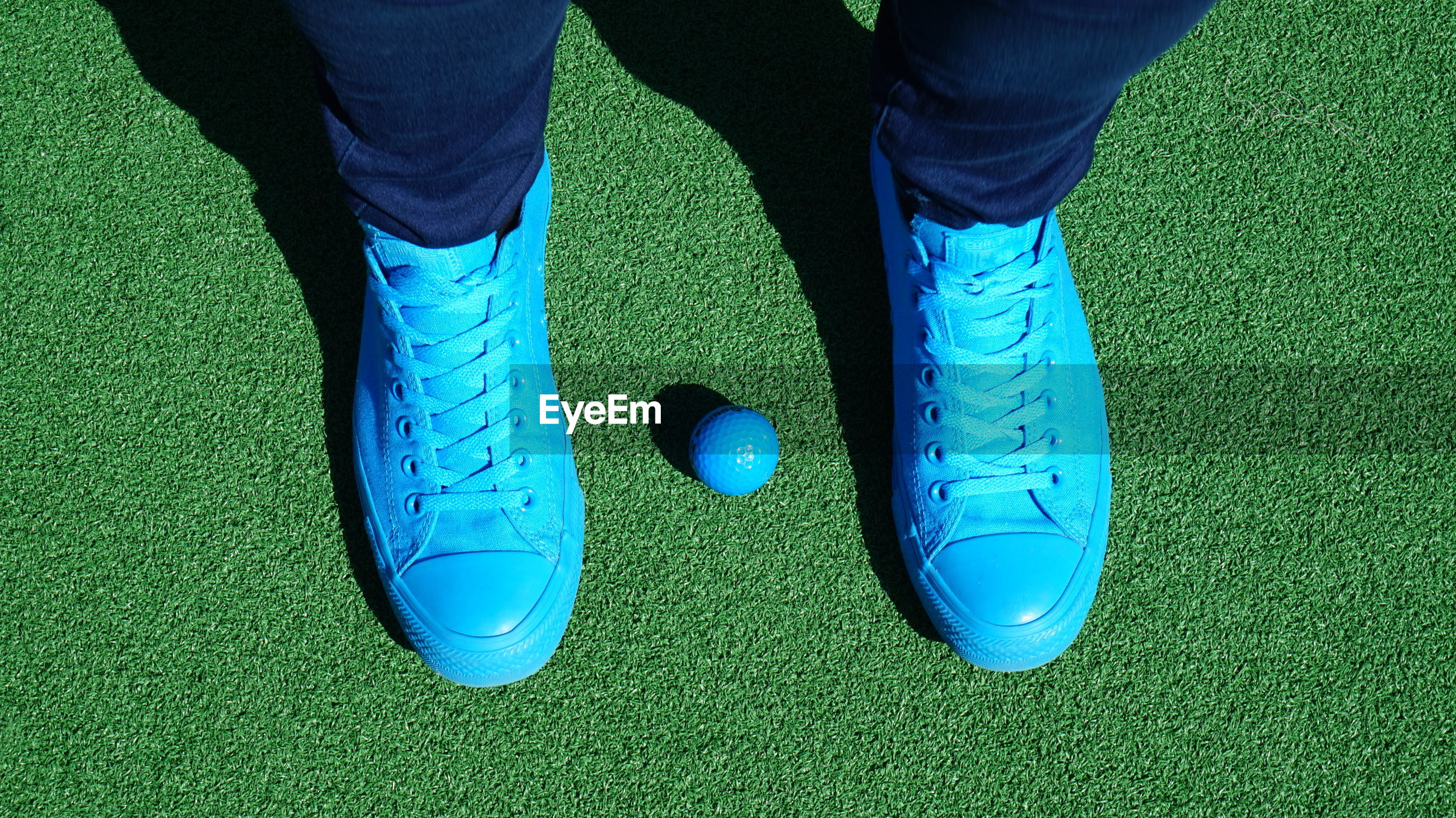 Low section of man standing with blue golf ball