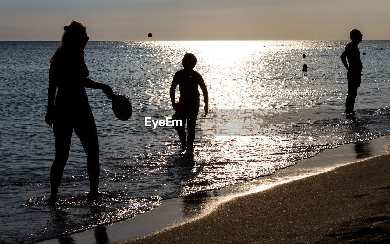 beach, water, sea, real people, shore, sand, sunset, lifestyles, leisure activity, wave, vacations, nature, horizon over water, beauty in nature, standing, silhouette, scenics, men, boys, reflection, fun, sky, playing, enjoyment, full length, sunlight, togetherness, outdoors, childhood, day, people