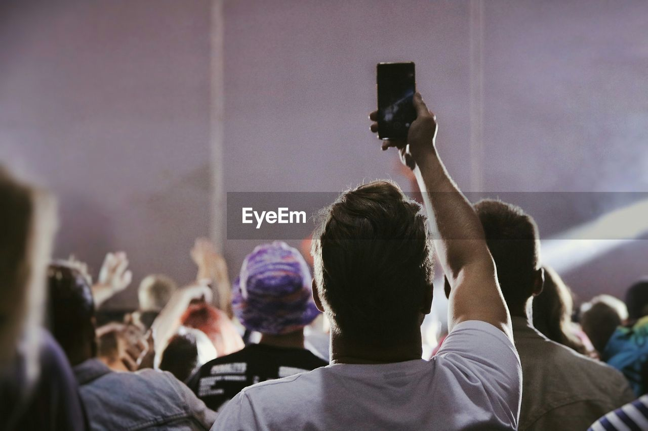 Rear View Of Man Photographing Using Phone At Concert